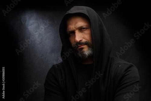 Cuadros en Lienzo  Portrait of a bald man with a beard in a black hood on a dirty gray background