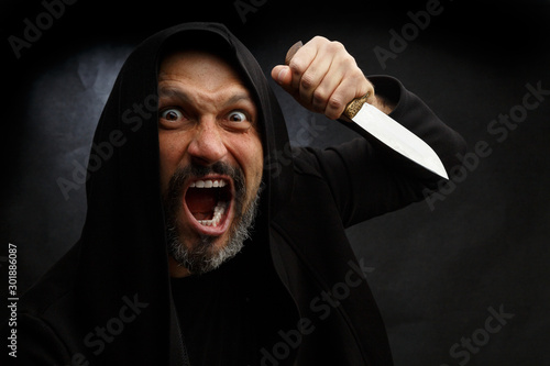 Photo  Portrait of a bald man with a beard in a black hood with a knife on a dirty gray background
