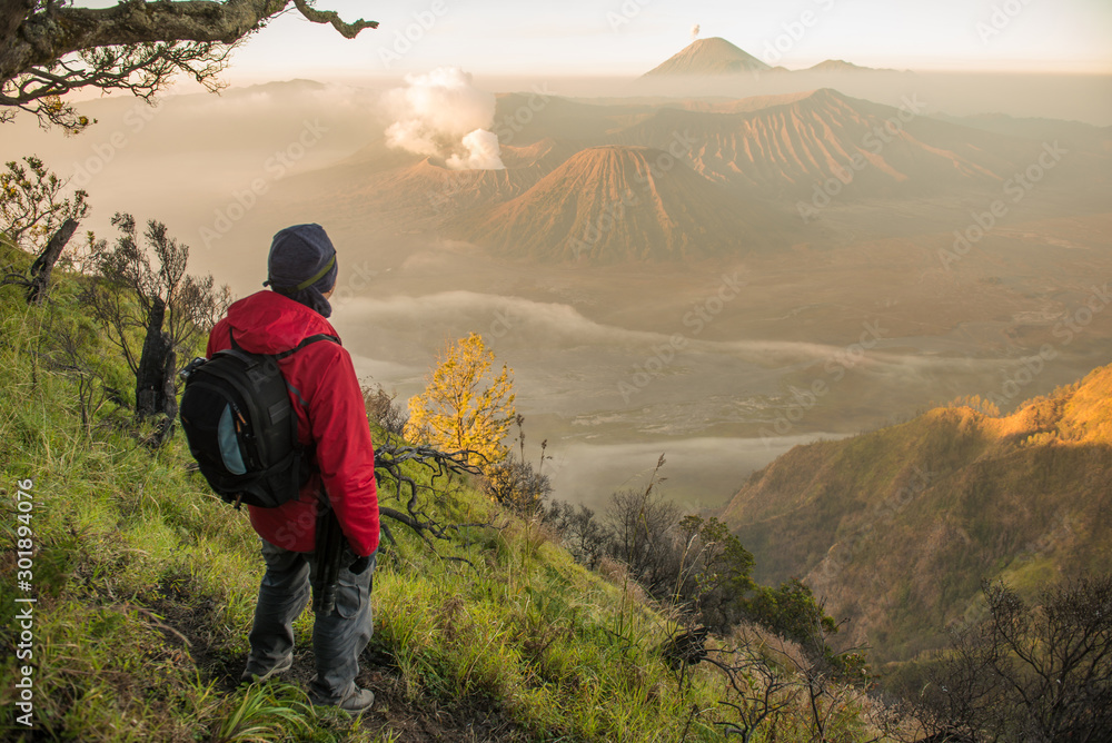 Fototapety, obrazy: Back view of tourist standing on the hill and looking to the beautiful sunrise of Bromo Tengger Semeru National Park in East Java, Indonesia.