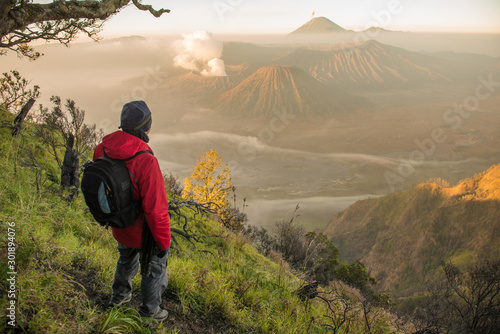 Fotografija  Back view of tourist standing on the hill and looking to the beautiful sunrise of Bromo Tengger Semeru National Park in East Java, Indonesia