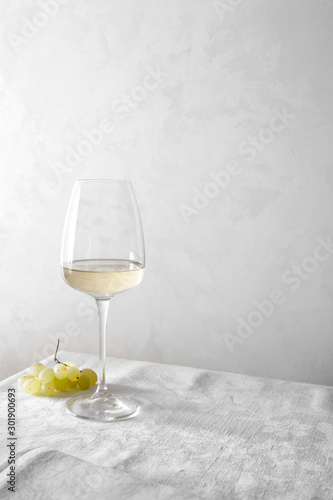 Poster de jardin Alcool White wine in a glass and a bunch of grapes on the table.