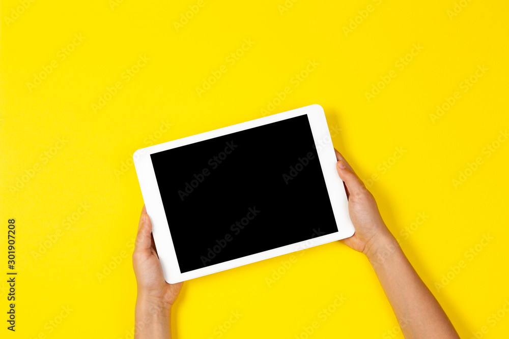 Fototapeta Kid hands holding white tablet computer on yellow background