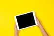 canvas print picture - Kid hands holding white tablet computer on yellow background