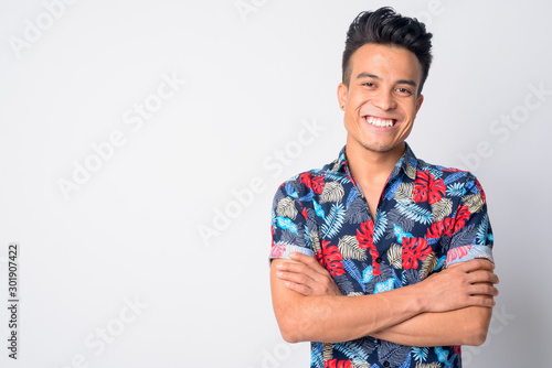 Obraz Portrait of happy young Asian man smiling with arms crossed - fototapety do salonu