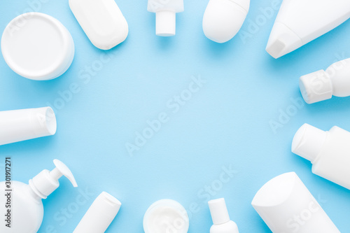 Fotomural  Different white toiletries on light pastel blue table