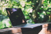A Laptop Computer On Wooden Balcony In The Garden