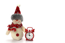 Snowman Toy Is Ready To Celebrate Christmas And New Year. Next To The Snowman Are A Red Clock, Which Is Almost Midnight. The Concept Is Time, A Snowman And Soon The New Year.