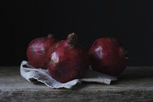 Still Life Photography Shot Of Three Gorgeous Pomegranates On A Wooden Deck