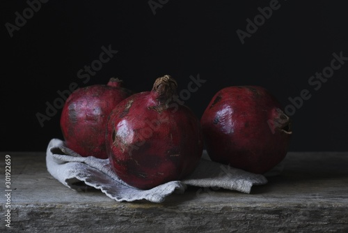 Fototapeta Still life photography shot of three gorgeous pomegranates on a wooden deck obraz