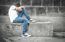 Caucasian Sad Boy Sitting In The Street.
