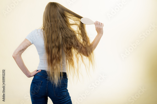 Blonde girl brushing her long hair