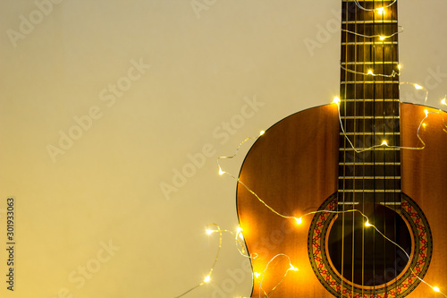 acoustic guitar wrapped in a luminous garland. Christmas gift Wallpaper Mural