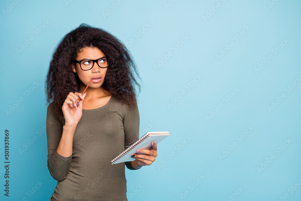 Fototapeta Hmm what to create. Portrait of clever smart intelligent mulatto girl hold pen write in note book diary think thoughts wear stylish outfit isolated over blue color background