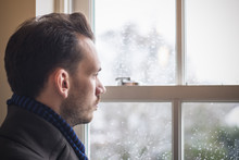 Portrait Of A Man Looking Out Window During Cold Winter