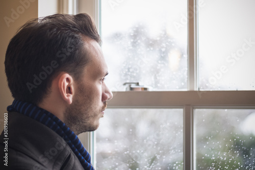 Portrait of a man looking out window during cold winter Canvas Print