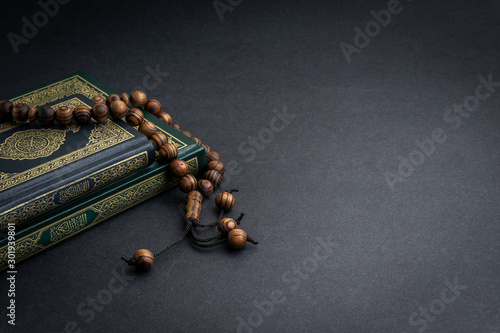 Canvastavla  Holy Quran with arabic calligraphy meaning of Al Quran and tasbih or rosary beads on black background