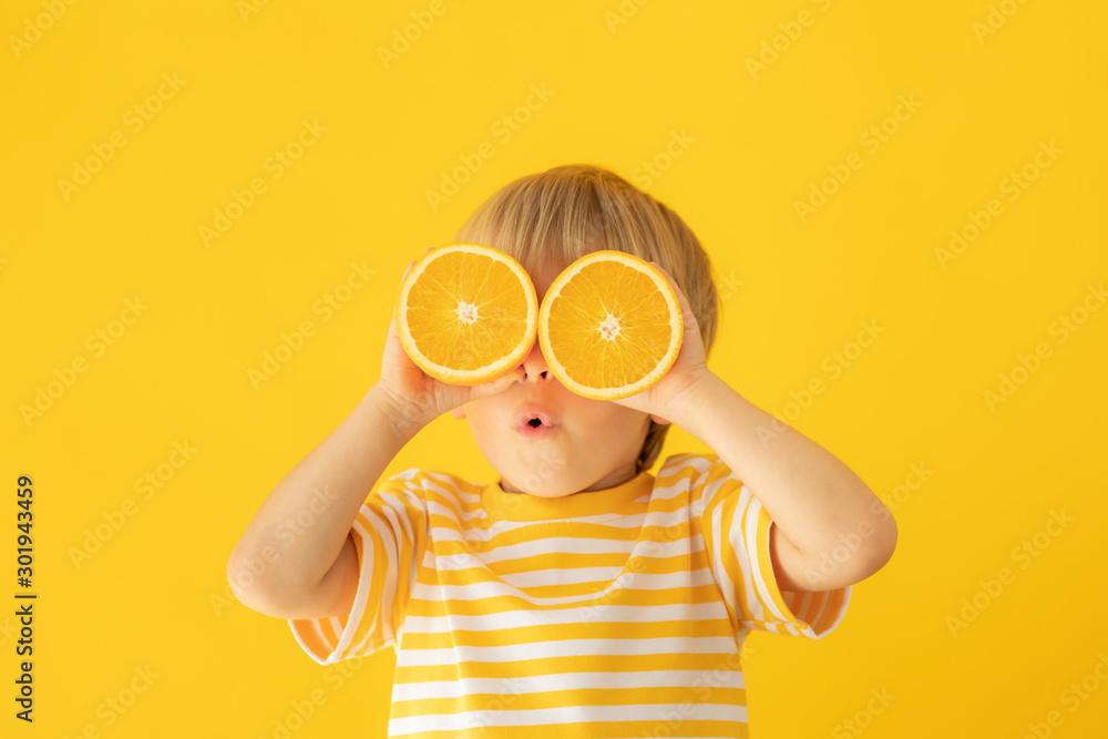 Fototapeta Happy child holding orange