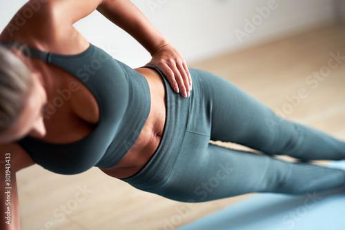Fototapeta Adult woman practising yoga at home obraz