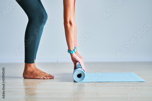 Obraz Young woman rolling yoga mat at home - fototapety do salonu