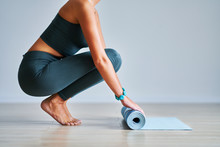 Young Woman Rolling Yoga Mat A...