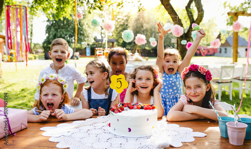 Obraz Children with cake standing around table on birthday party in garden in summer. - fototapety do salonu