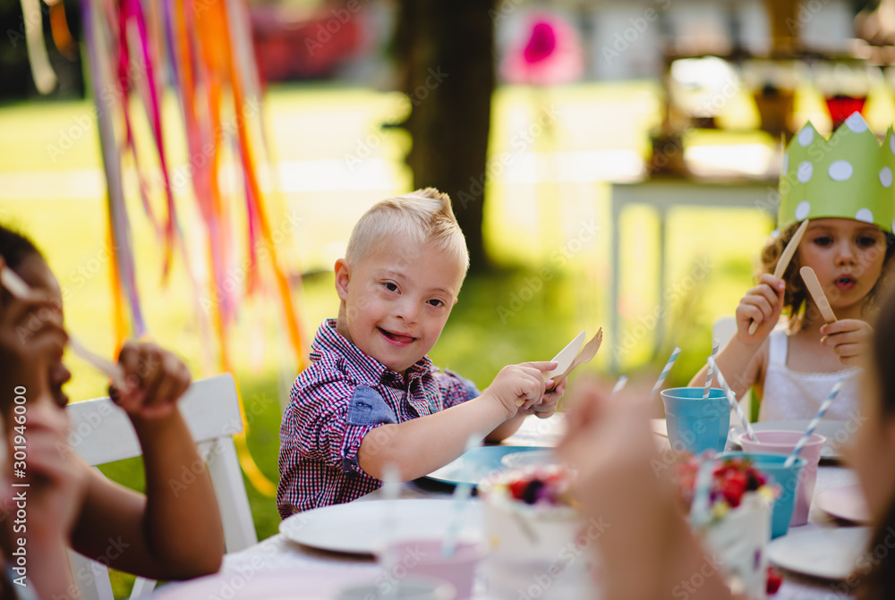 Fototapety, obrazy: Down syndrome child with friends on birthday party outdoors in garden.