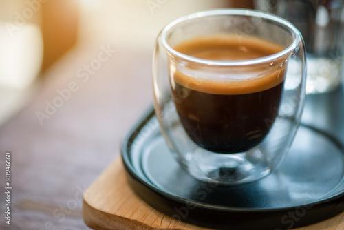 фотография Hot espresso coffee in a clear glass, in retro coffee shop.