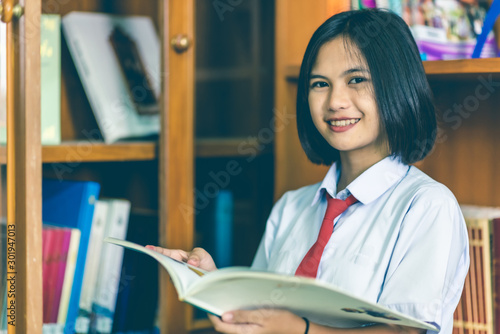 Photo Asian high school female students with short hair in a white school uniform, red necktie, studying in the school library that made of wall-mounted bookcase with wood patterns