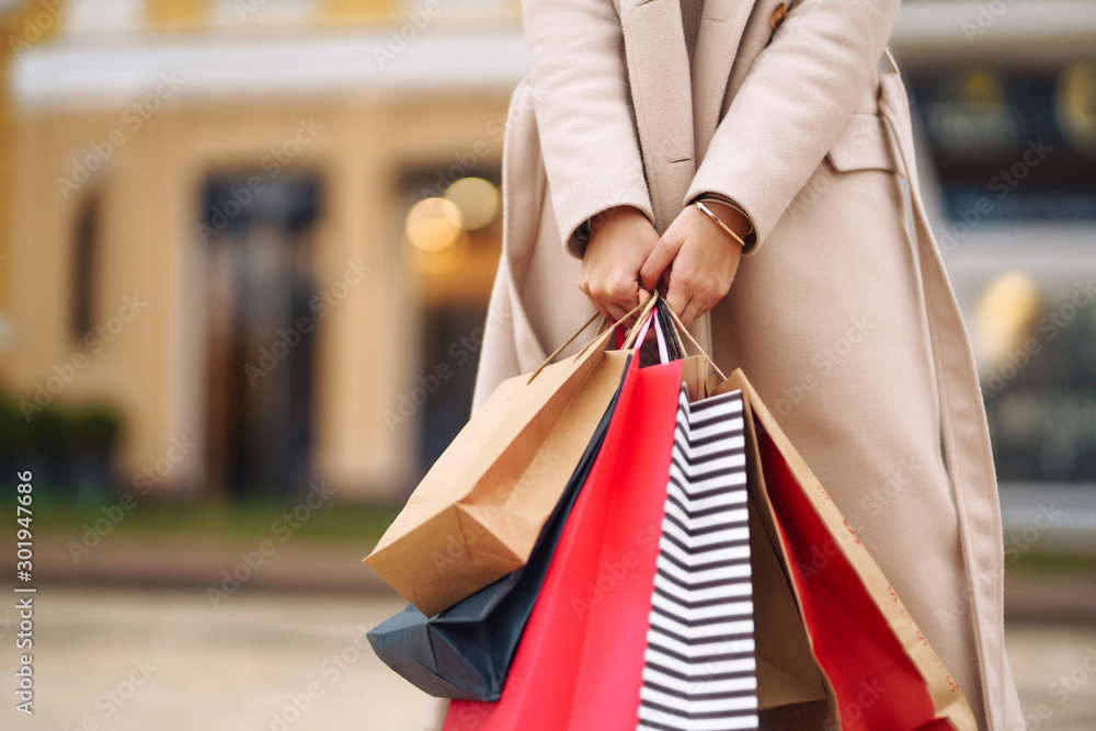 Fototapeta Shopping bags in the hands. Hand of young woman with multi-coloured bags with purchases. Beautiful girl holding shopping bags on the city street. Consumerism, shopping, sales, lifestyle concept.