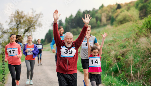 Large group of multi generation people running a race competition in nature Fototapeta