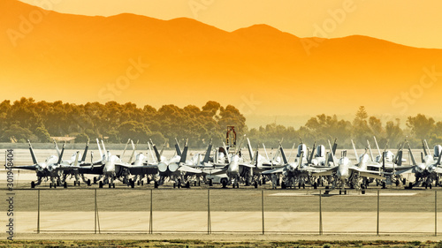 military fighter jet storage facility at airport against mountain landscape background on sunset Wallpaper Mural