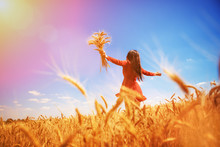 Happy Woman Enjoying The Life In The Field Nature Beauty, Blue Sky And Field With Golden Wheat. Outdoor Lifestyle. Freedom Concept. Woman Jump In Summer Field