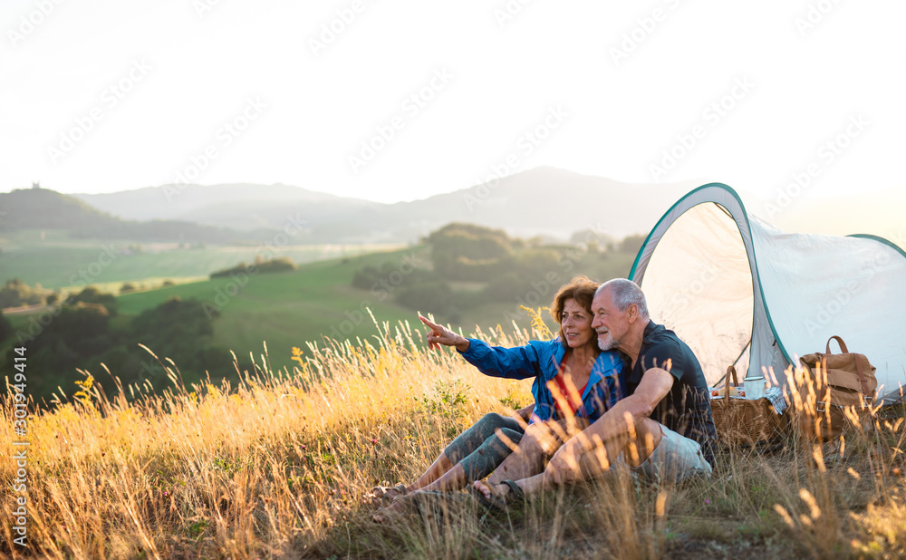 Fototapety, obrazy: Senior tourist couple in love sitting in nature at sunset, resting.