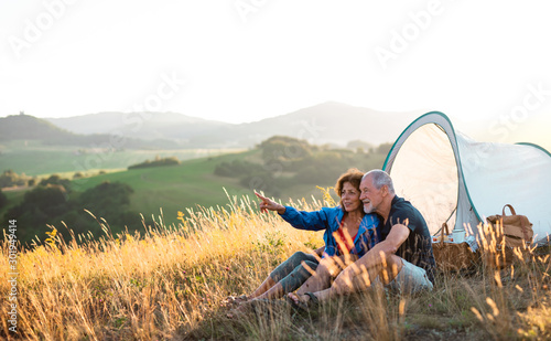 Obraz na plátně  Senior tourist couple in love sitting in nature at sunset, resting