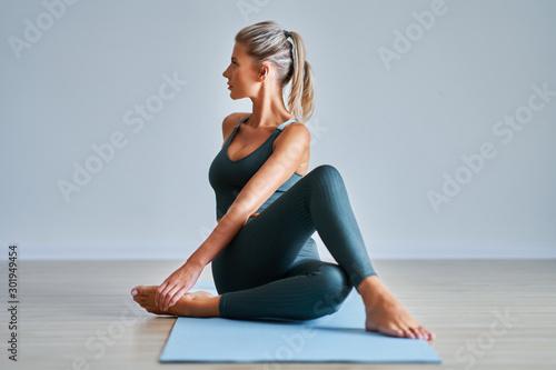 Obraz Adult woman practising yoga at home - fototapety do salonu