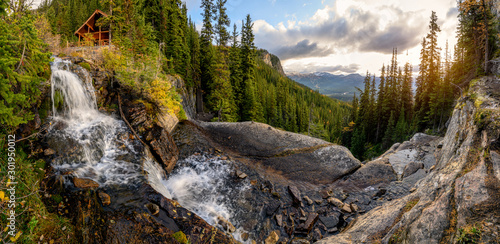 Obraz Scenery of Tea house on waterfall flowing in pine forest at Banff national park - fototapety do salonu