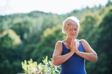 A Senior Woman Standing Outdoors On A Terrace In Summer, Doing Yoga Exercise.