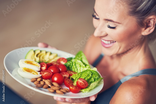 Adult woman eating healthy lunch and sitting on yoga mat Canvas Print