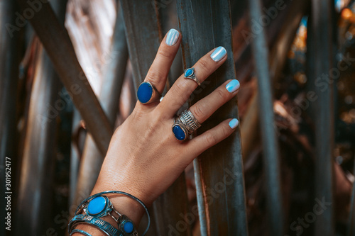 Fotografie, Tablou  close up of woman hand with gemstone rings on tropical background