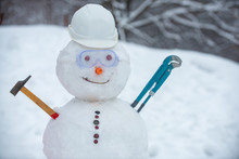 Snowman Worker On Snow Background. Funny Snowman In Work Helmet On Snowy Field. Handmade Snowman In The Snow Outdoor.