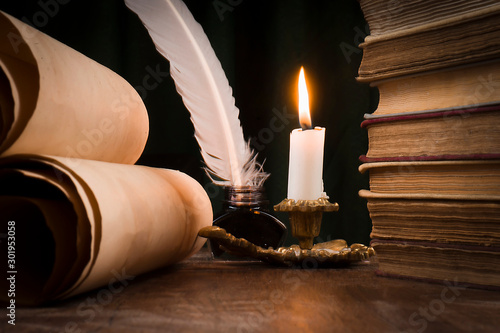 Scrolls of parchment, a stack of books, and a lit candle Slika na platnu
