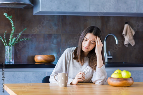 Brunette girl is sitting at table in kitchen and holding hand on head temple Wallpaper Mural