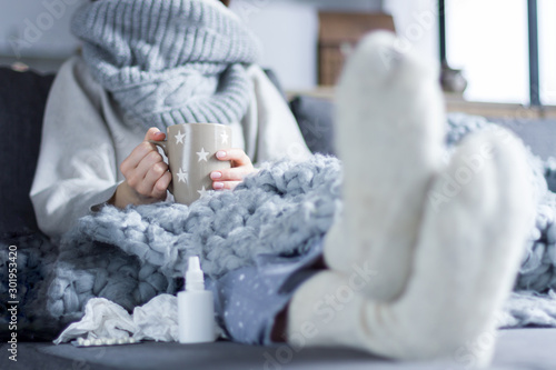 Pinturas sobre lienzo  Sick girl in scarf and knitted socks is sitting in bed sofa wrapped in grey blanket