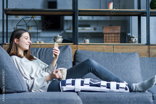 Cuadros en Lienzo Smiling brunette girl with broken leg is sitting on couch sofa, resting and drinking tea at home