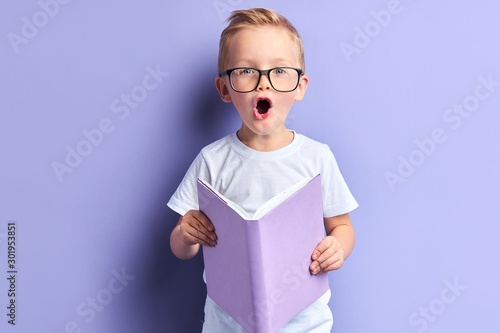 Obraz Lovely boy wearing white t-shirt and glasses on eyes reading book with purple cover, stand in shock after reading, bright emotions of kid boy. Isoated over purple background - fototapety do salonu