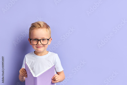 Vászonkép Clever kid wearing white t-shirt and glasses on eyes smiling look at camera