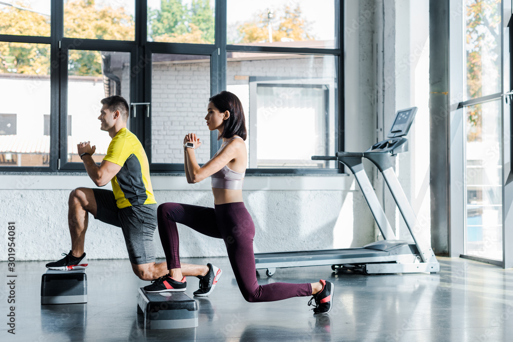 Fototapeta side view of handsome sportsman and sportswoman doing lunges on step platforms in sports center