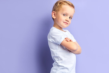 Side view on cute little boy posing isolated over purple background, looking at camera. Portrait