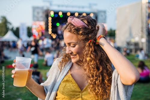Fototapeta A young woman with drink dancing at summer festival. obraz