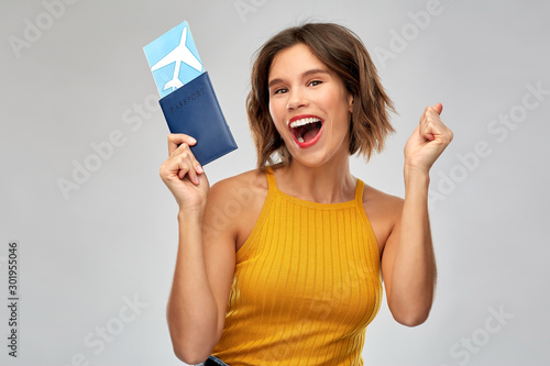 Obraz travel, tourism and vacation concept - happy laughing young woman in mustard yellow top with air ticket and passport over grey background - fototapety do salonu